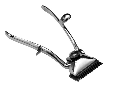 A vintage manual hair clipper in stainless steel isolated on a white background. photo