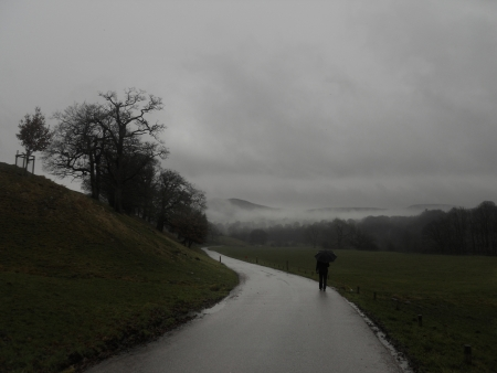dreary: A lone figure walks along a tarmac road in low cloud and rain  Stock Photo