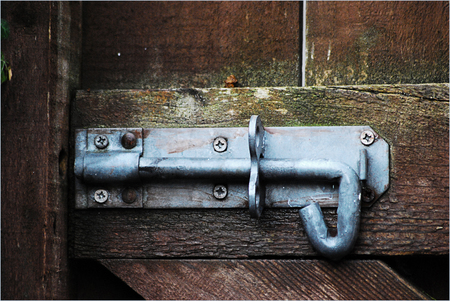 A galvanised metal slide bolt attached to a rough wooden garden gate