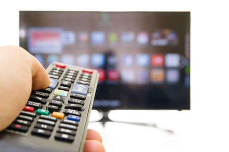 Smart tv and hand pressing remote control photo