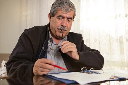 man  glasses: Senior Man Signing Papers