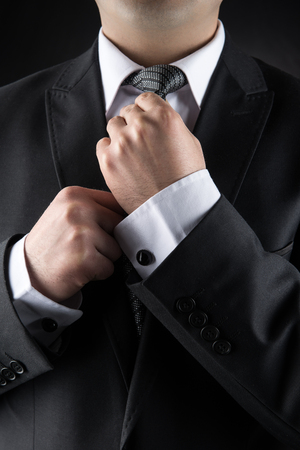 man in suite: Businessman Correcting Tie Stock Photo