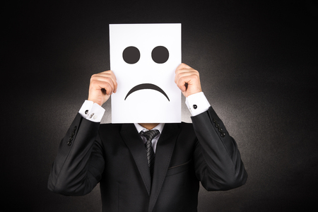 crestfallen: Businessman holding paper with sad emoji