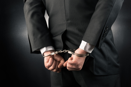 restraining device: Businessman is arrested and handcuffed