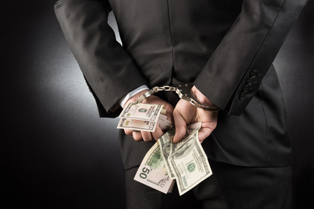 arrested: Businessman is arrested and handcuffed with dollar Stock Photo