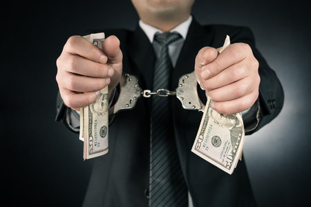 restraining device: Businessman is arrested and handcuffed with dollar Stock Photo