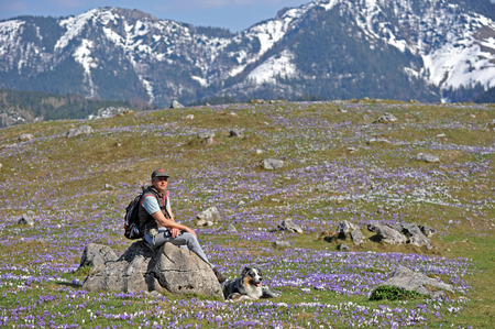 Frau mit Hund genießen Bergweg im Frühjahr