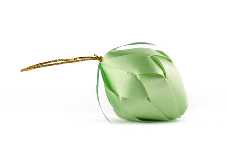 Coin folding with Ribbon is shaped a green fruit isolated on white background for ordination scatter ceremony of buddhism.