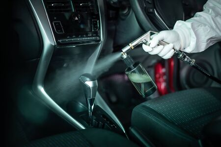 Clean surfaces in car with a disinfectant spray. Help kill coronavirus in  car after going out.