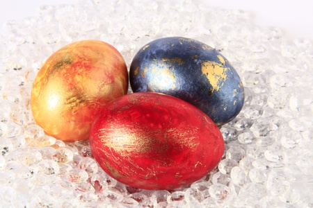 unorthodox: three Easter Eggs in red, blue and yellow on decorative plastic gravel Stock Photo