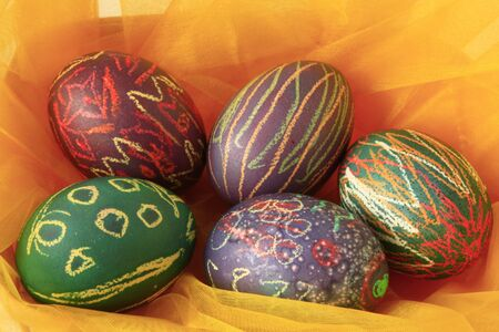 unorthodox: colorful Easter Eggs in a nest made from tulle Stock Photo