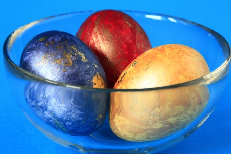 unorthodox: three Easter Eggs in the colours red, yellow and blue, before blue background