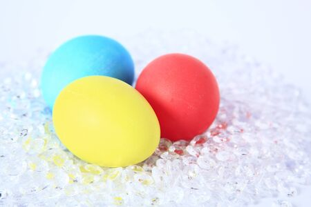 unorthodox: three colored Easter eggs on decoration gravel