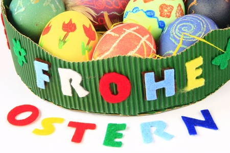 Ostern: Easter nest with writing Frohe Ostern (happy Easter) with colorful Easter eggs