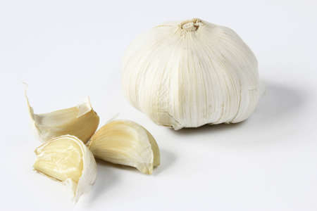 strikingly: Garlic, whole bulb and three individual cloves against a neutral background