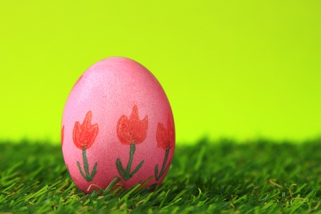 Easter decoration from single, brightly painted, Easter egg in green artificial turf photo