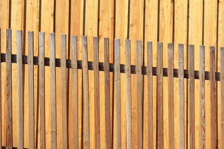 Lattice fence in front of a wall made of fresh wood planks photo