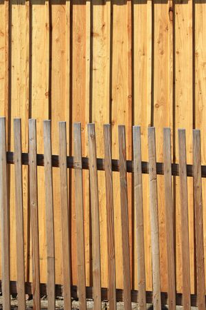 Lattice fence in front of a wall made of fresh wood planks Stock Photo - 13331817