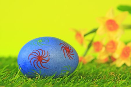 Easter decoration from single, brightly painted, Easter egg in green artificial turf before blurred daffodils Stock Photo - 14163375