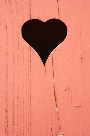 Heart shape cut out of a wall of wooden planks photo