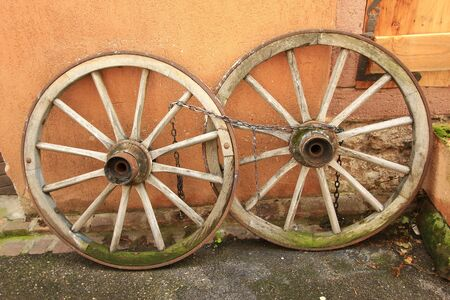 carreta madera: viejas ruedas de carreta de madera apoyado contra una pared, Alsacia, Francia