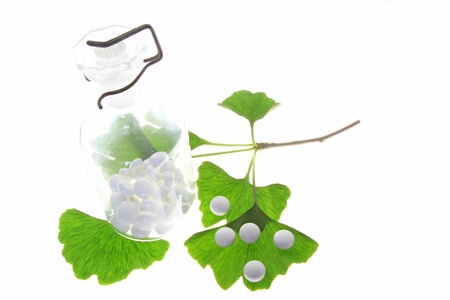 ginkgo tree: Leaves of the ginkgo tree  Ginkgo biloba  and coated tablets for oral use  symbolic  against a white background