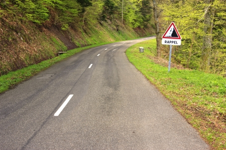 Country road in the Vosges Mountains, Alsace, France with the French road signs  rock fall  and the additional sign  RAPPEL  photo