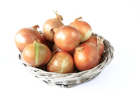 close up of onions in a basket: Onions in a basket before a white background