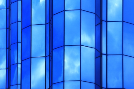 futuristically: modern facade in which blue sky and clouds are reflected Stock Photo