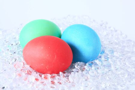 unorthodox: Three Easter eggs in a modern nest of plastic decoration gravel Stock Photo