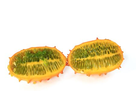 hedged: Horned melon  Cucumis metuliferus  in longitudinal section, isolated against a white background Stock Photo