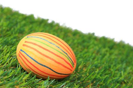 pasto sintetico: Coloridos huevos de Pascua teñidos sobre césped sintético en frente de un fondo blanco