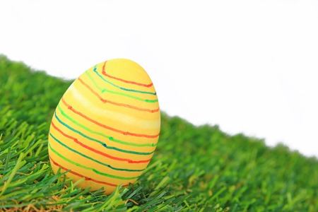 Colorful dyed Easter egg on synthetic grass in front of a white background