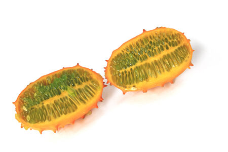 hedged: Horned melon, Cucumis metuliferus in longitudinal section, isolated against a white background Stock Photo