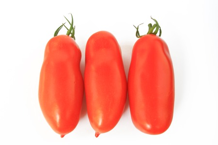 oblong: Three ketchup tomatoes, isolated against white background