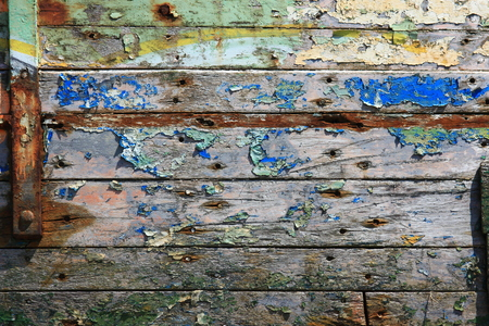 repeatedly painted and weathered wood planks of a shipwreck photo