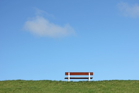 dike: Bench on a dike at the North Sea with blue sky, Germany