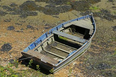 oude roeiboot afgemeerd op het kiezelstrand bij eb