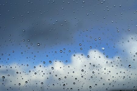 window pane: Raindrops on a window pane against a blue sky with clouds