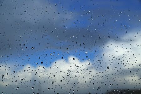 pane: Raindrops on a window pane against sky with clouds Stock Photo