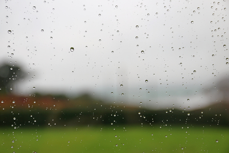 Raindrops on a window pane, blurred landscape in background