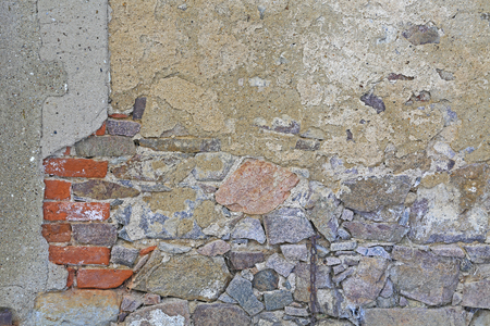 Background - old wall of natural stone and bricks with peeling plaster