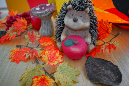 A figurine of a hedgehog with autumnal background Stock Photo