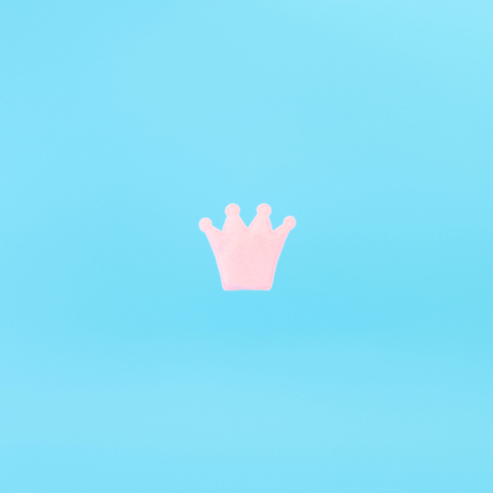 Pink crown on a blue background. Minimal concept photo. Avatar.