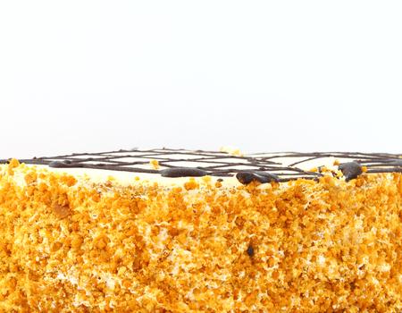 Honingstaartclose-up. Pastei die met chocolade op een witte achtergrond wordt verfraaid.