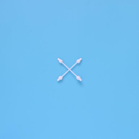 Patroon van katoenknoppen, swabs met limiter op een blauwe achtergrond. Plat leggen minimaal concept.