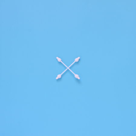 Pattern of cotton buds, swabs with limiter on a blue background. Flat lay minimal concept.