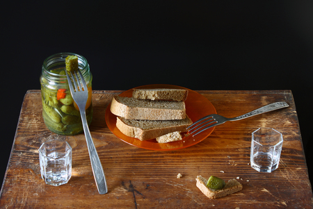 Feast for two. Vodka, black bread, salted cucumber on a wooden background. Binge and  appetizer in Russian style.