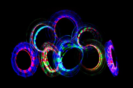 poi: Abstract light painting taken while spinning bright coloured glowing poi in circles  Stock Photo