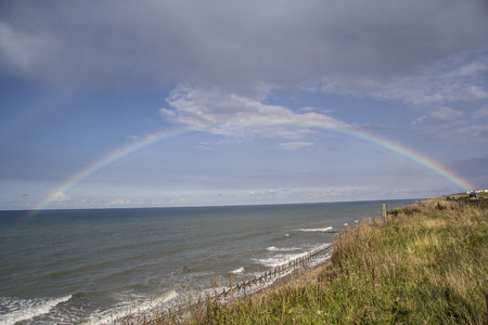 Photo of a rainbow over the sea. Taken on the cliff tops in between Sheringham and Cromer UK. photo